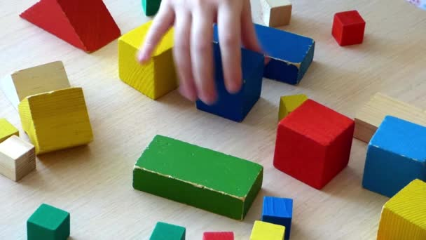 Two Caucasian kids playing together with wooden bricks  Children  constructing house from colored elements  Bright toy building - real estate  theme  Closeup view