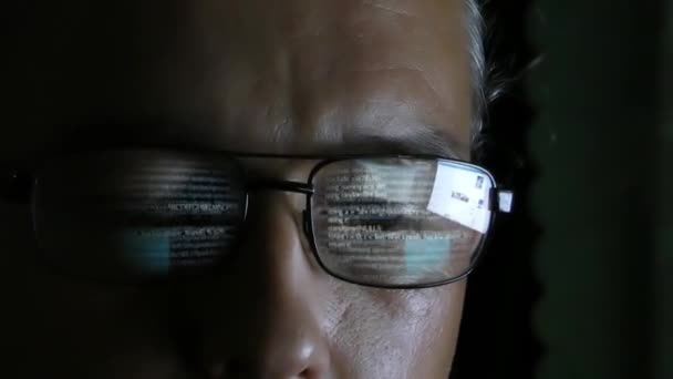 Programmer or hacker in glasses looking on monitor - software code reflecting in the glass. Caucasian man in dark room working with computer. Digital technologies.