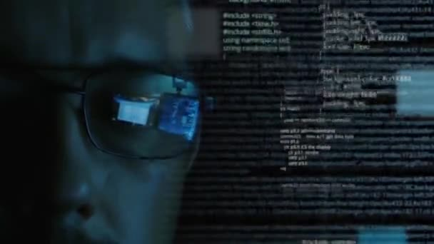 Programmer or hacker in glasses looking on monitor - software code reflecting in the glass and flying around. Caucasian man face in the dark. Digital technologies.