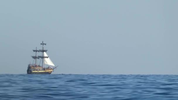 Stylizované pirátské lodi na moři. Plachetní loď pohybující se ve vodě na obzoru. Slunečný letní den, Černého moře nedaleko Soči.