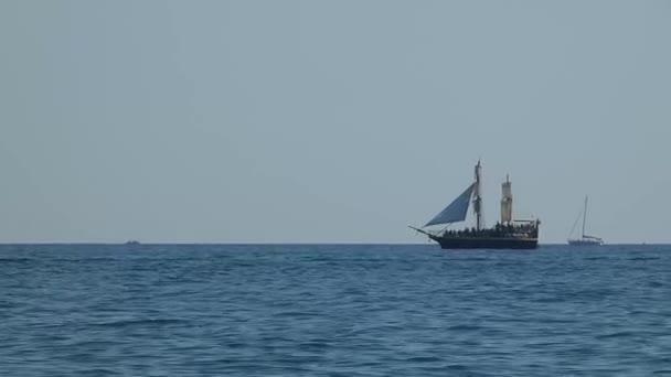 Stylizované pirátské lodi na moři. Plachetní loď pohybující se ve vodě na obzoru. Slunečný letní den, Černého moře nedaleko Soči
