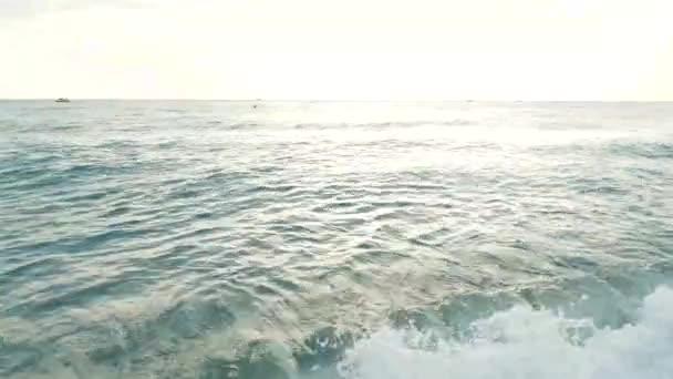 Tiszta víz hullámai, Vértes megtekintése. Tengeri surf Beach. Fehér hab a vízben. Napsütéses nyári este. Természetes háttér.
