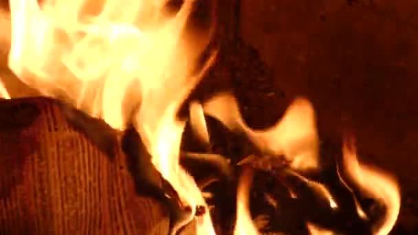 Papír s rozmazaný text pálení v ohni. Detailní pohled na červené horké zářící plamen uvnitř kamen. Uhlíky a dokumenty v peci nebo táborák. Abstraktní pozadí
