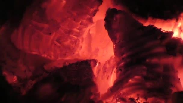 Žhnoucí uhlíky. Detailní pohled na červené horké zářící dřeva uvnitř kamen. Uhlíky a oheň v peci nebo táborák. Abstraktní pozadí
