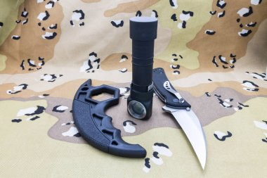Military set of knife, brass knuckles and a lantern on a camouflage background.