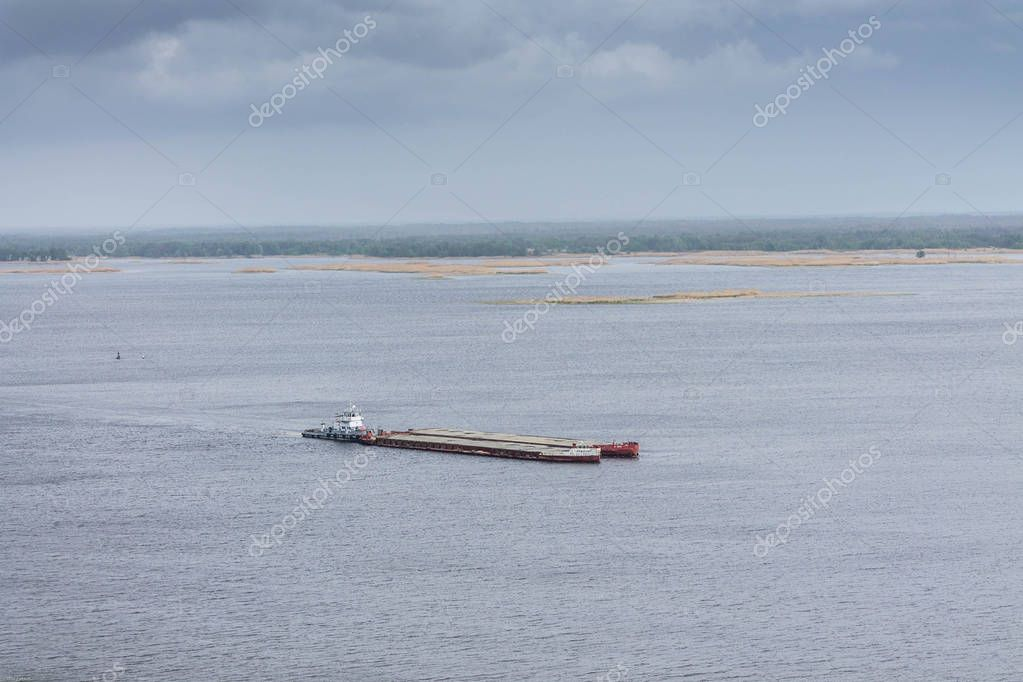 An industrial barge carries cargo across the river. A floating ship. Hoisting, industrial ship.