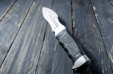 Military knife with black handle of leather. Blacl background.