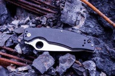 The knife is folded. Knife blade with a hole. A knife on the rocks.