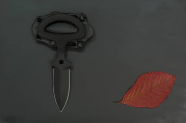 Military autumn. Autumn leaf and black knife on a black background. Fall of the leaf.