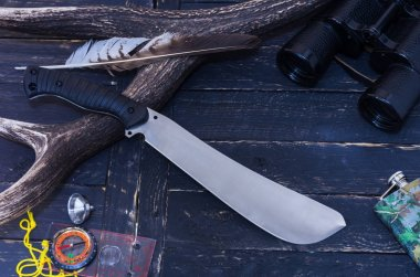Knife hunter. Machete on the background of the horn. Deer horn, compass and feather.