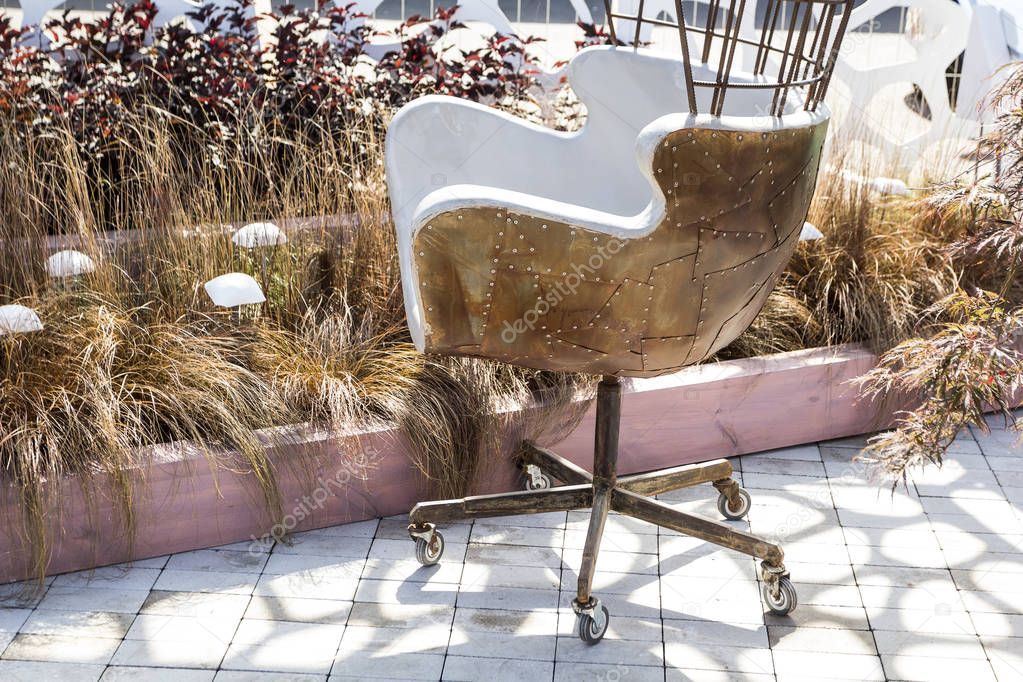Designer metal chair with rivets and rust with wheels.