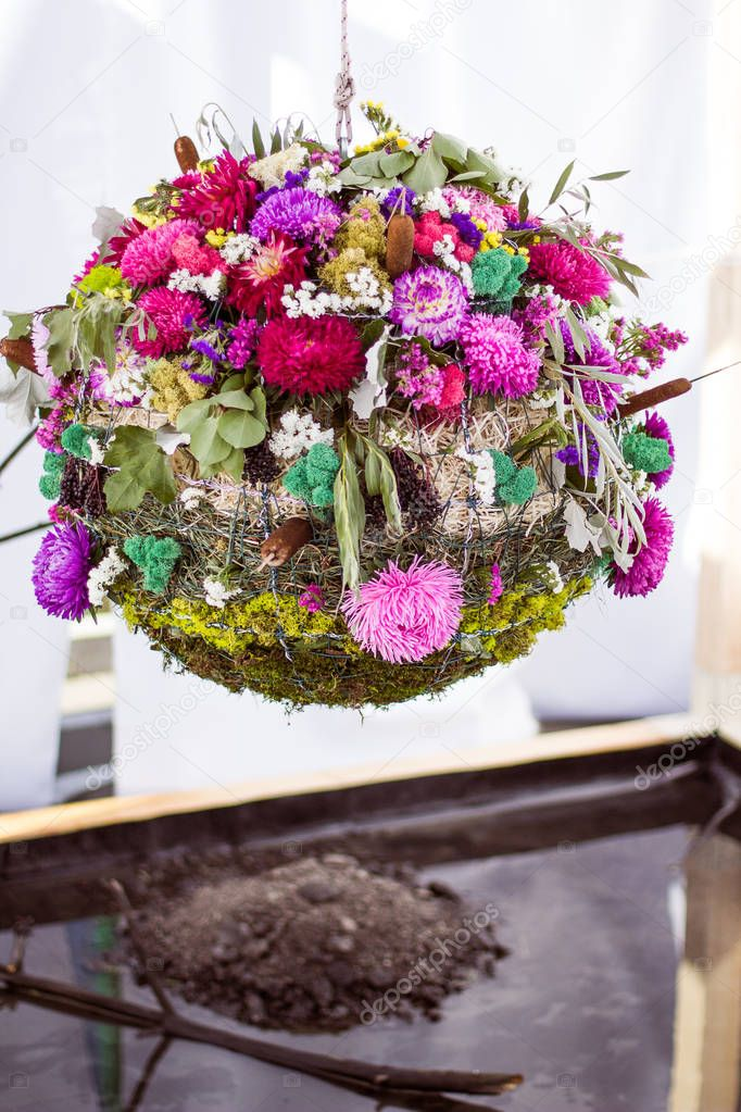 Designer wedding ball of flowers, moss and grass called water.