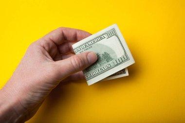 Bent yüz dolarlık banknot elinde açık bir sarı arka plan, satış veya