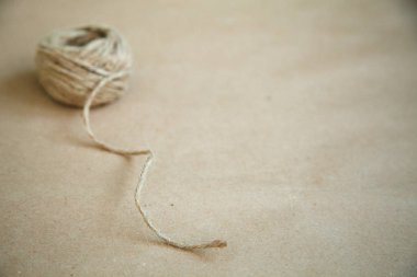 Skein of jute twine on the recycled paper background. Copy space