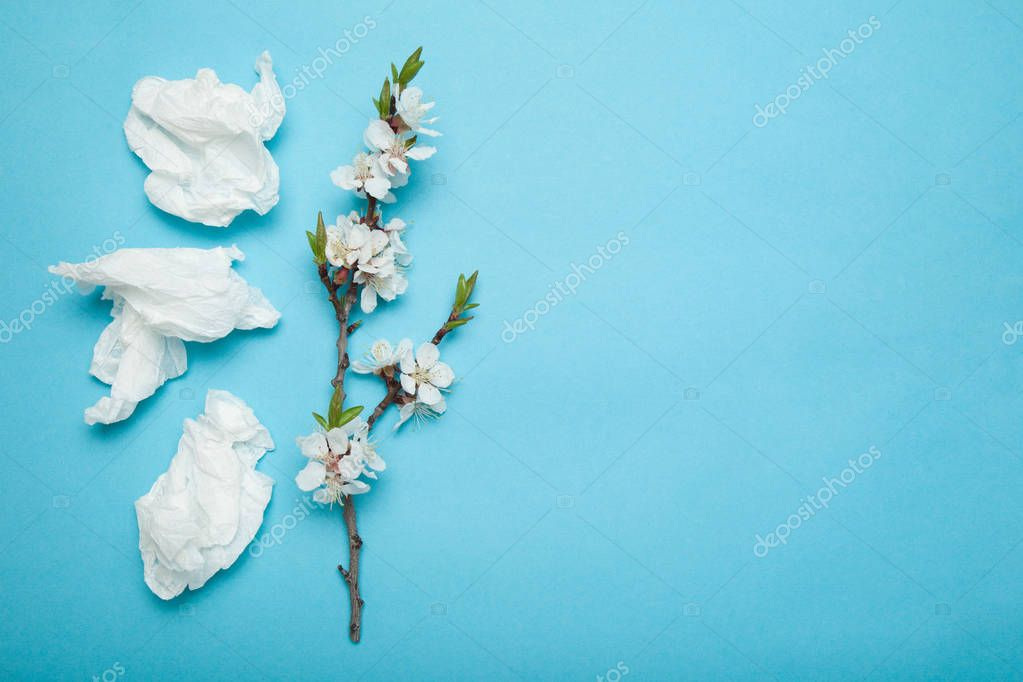 Allergy concept on blue background, white used napkins and flowe