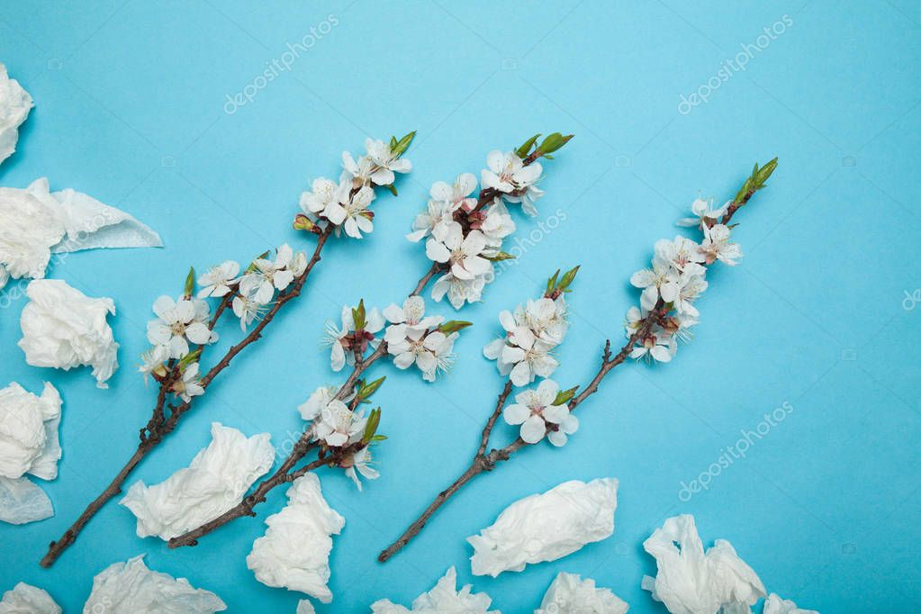 Allergy concept, white used napkins and flowers.