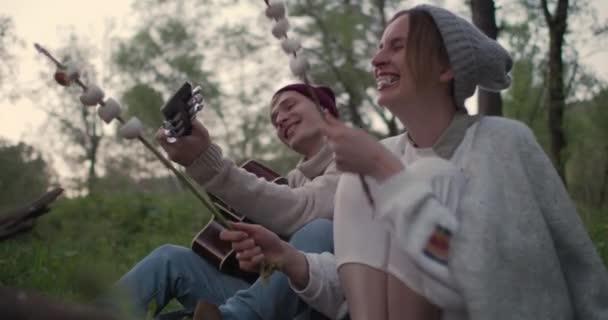 Egy fiatal házaspár ül a tűz, sütés marshmallows, nevetve hangosan és jól érzik magukat.