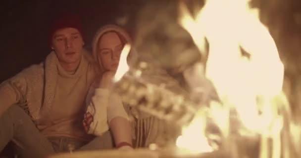 Egy fiatal pár ül éjjel az erdőben, magába foglaló közös kockás előtt egy tábortűz, beszéd és nevetve.