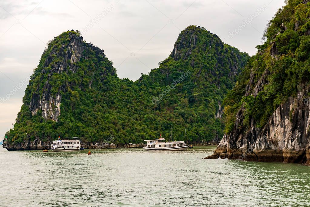 Tour Boats on Halong bay navigate past large rock formations.