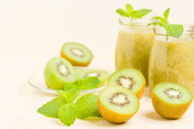 Kiwi smoothie decorated with fresh green mint leaves and raw ripe cut fruit on yellow pastel background - transparent jars of blended vitamin cocktail for healthy food concept.