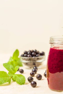 Currant smoothie decorated with fresh green mint leaves and raw ripe berries on yellow pastel background - transparent jars of summer blended vitamin cocktail for healthy food concept.