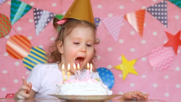 Dítě dívka sfoukne svíčky na narozeninový dort a jí svým prstem. Dítě dělá přání
