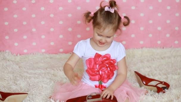 Glamour. Módní. Módy. Roztomilá holčička šaty červené brýle ve tvaru srdce. Růžový pozadí. Funny dítě úsměv a smích