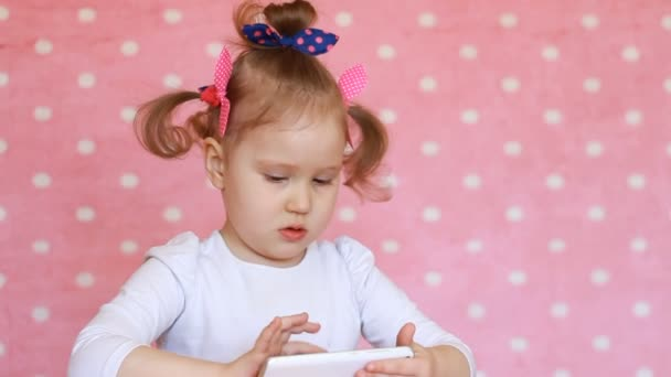 Child girl playing with a mobile phone. Baby uses a game application on the smartphone.