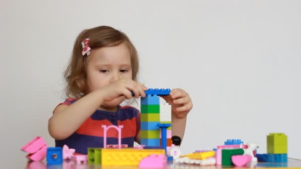 The child is busy building a constructor. Baby girl playing a game