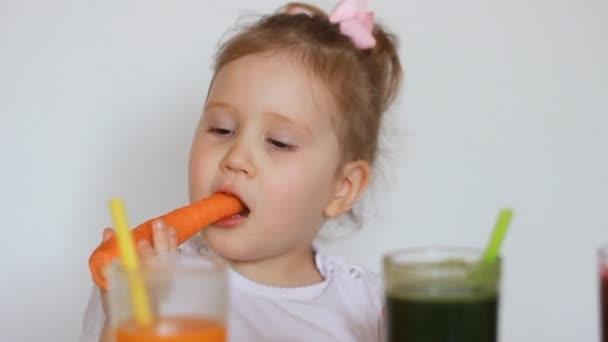 Vegetariánské dítě sní ovoce a zeleniny - mrkev a kiwi, smoothie nápoje