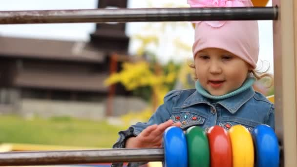 Child girl plays in the playground and learns to count in the game.