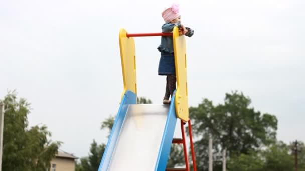 Dítě dívka vystoupí tak vysoko nahoru. Dětské hry na hřišti