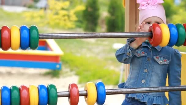 Child girl plays in the playground and learns to count in the game. Development of preschoolers.