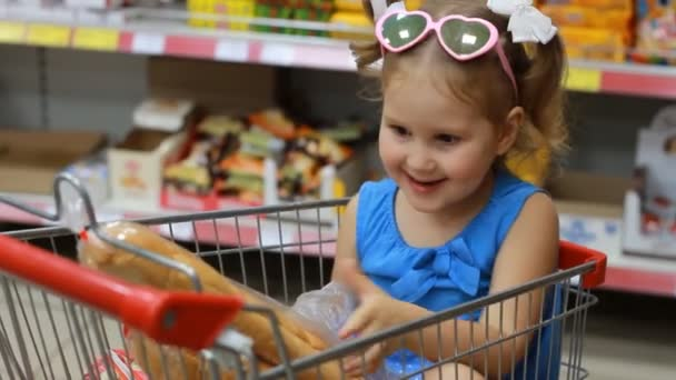 Child girl sits in a trolley for products in the store and holds a baguette. Baby shopping