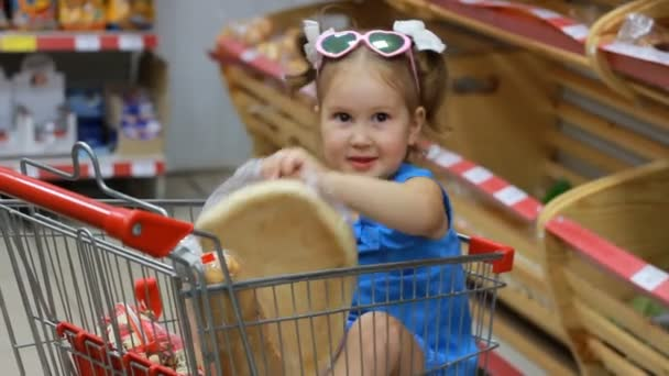 Child girl sits in a trolley for food in the supermarket and holds a bread. Baby shopping