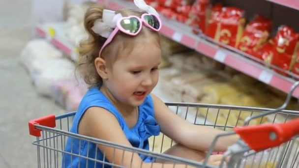 Child girl sits in a trolley for food in the supermarket and holds a pasta. Baby shopping