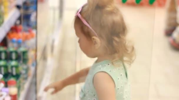 Dítě dívka v úložišti otevře dveře chladničky a koupí dětské výživy. Nakupování v supermarketu