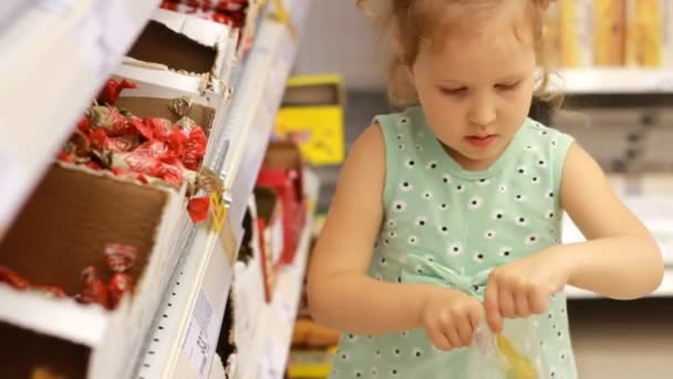 Child in the supermarket buys candies and sweets. Shopping store warehouse