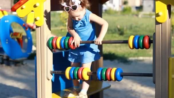 Dítě dívka hraje na hřišti v různých hrách. Zábava pro děti. Vývoj předškoláků. Chodící dítě za slunečného dne