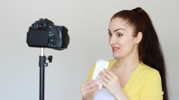 Dívka blogger inzeruje mobilní telefon. Reklamní smartphone pro Internet