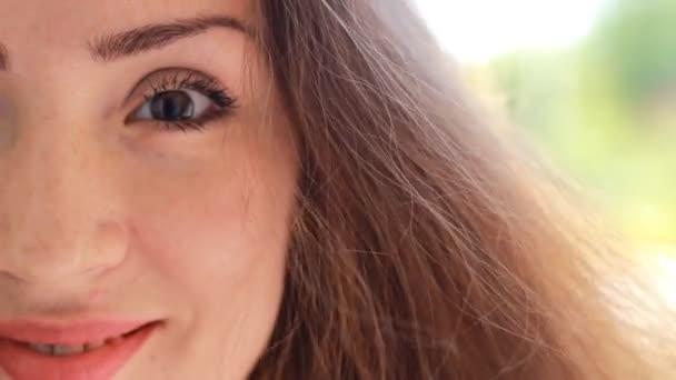Detailní portrét polovinu tváře krásná mladá žena s hnědými vlasy, na větrný den