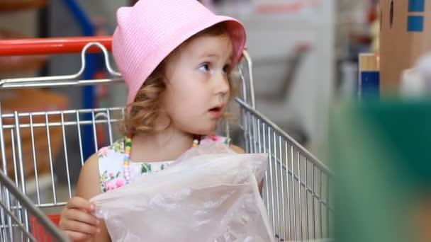 Dítě dívka v úložišti rozhodne ovoce. Supermarket s potravinami a nákupní vozík