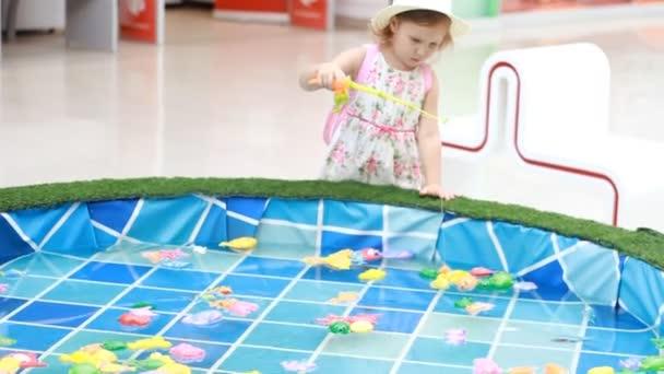 Kind Mädchen auf dem Spielplatz spielt ein Spiel von Fischen, fängt die Fische im Pool und in einen Eimer Pfähle