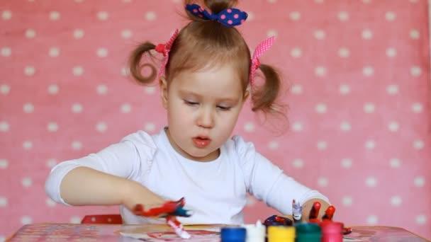 Gyermek lány rajz ecsettel és festékkel. Baba art. Gouache és festék
