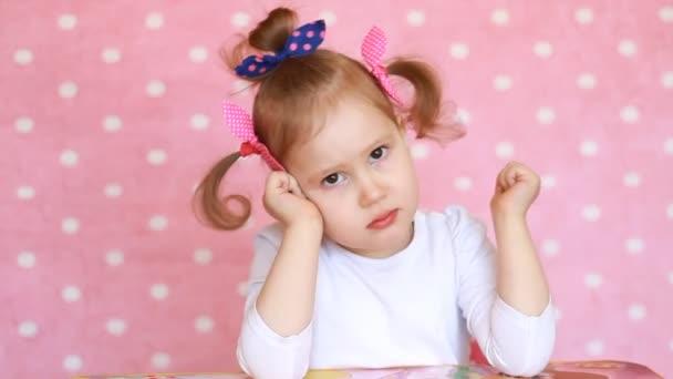 Dítě dívka na kameru. Portrét roztomilé dítě na růžovém pozadí detail