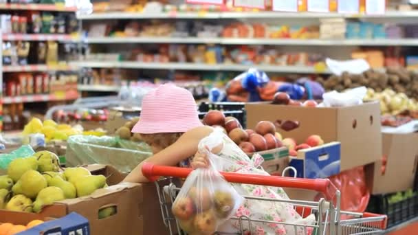 Child girl in the store chooses fruit pears. Grocery supermarket and shopping trolley