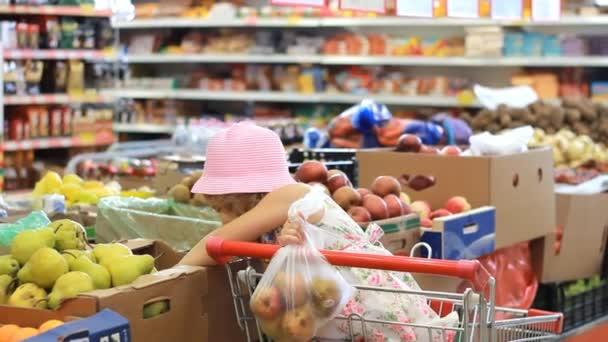 Dítě dívka v úložišti rozhodne ovoce hrušky. Supermarket s potravinami a nákupní vozík