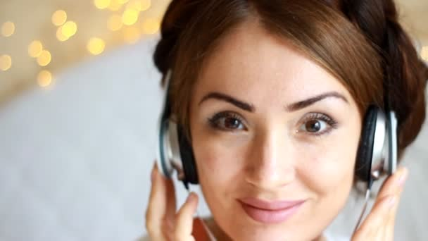 Beautiful woman in headphones listening to a musical song on light background