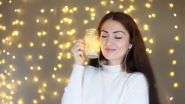 Woman in headphones smilling, listening to music, looking at the lights,  closes her eyes and relaxes  Background with bokeh lights