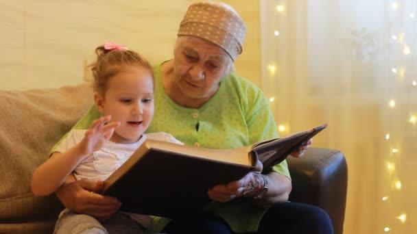 Babička a vnučka dohromady, čtení pohádky kniha. Prababička huging její pravnučka
